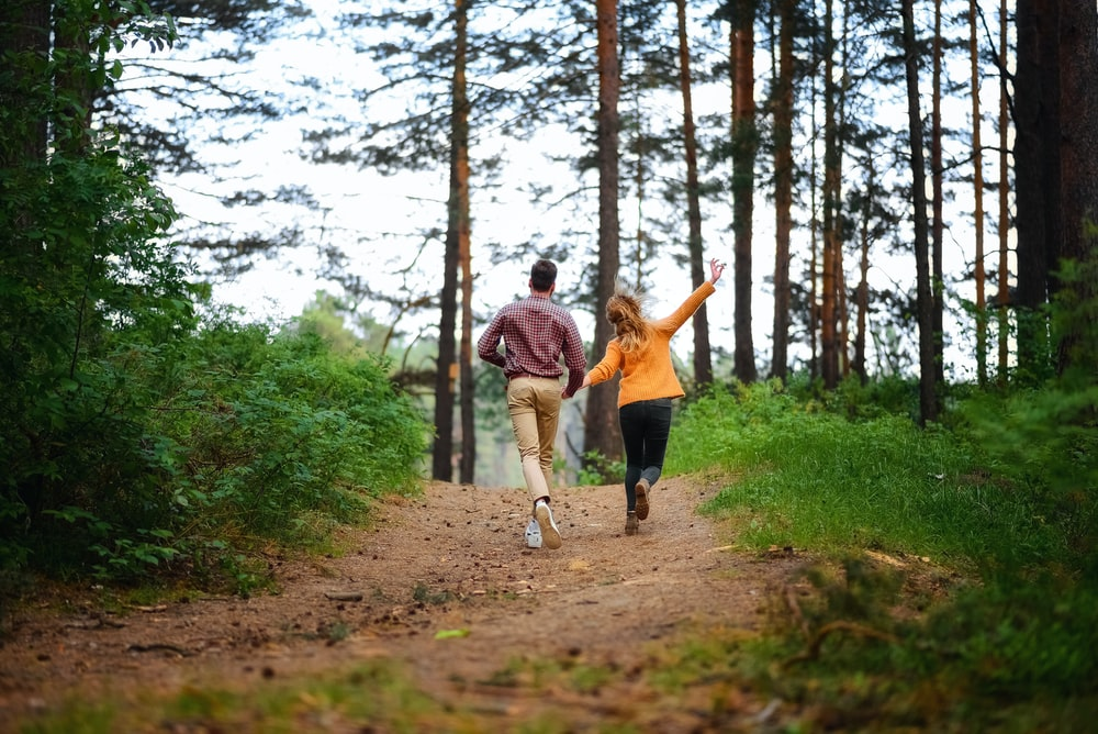 man and woman walking on forest