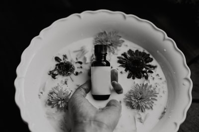 grayscale photo of person holding bottle