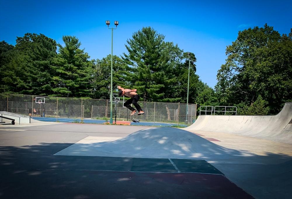 man skateboarding near trees
