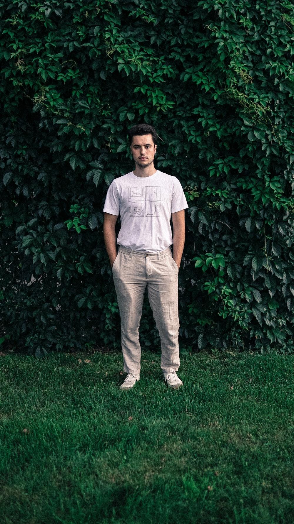 man wearing white shirt standing on grass lawn