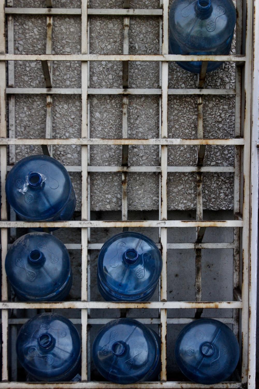 seven blue plastic carboys