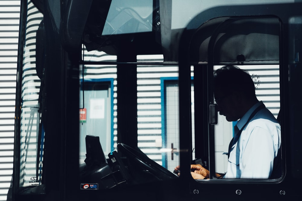 silhouette photography of man driving bus