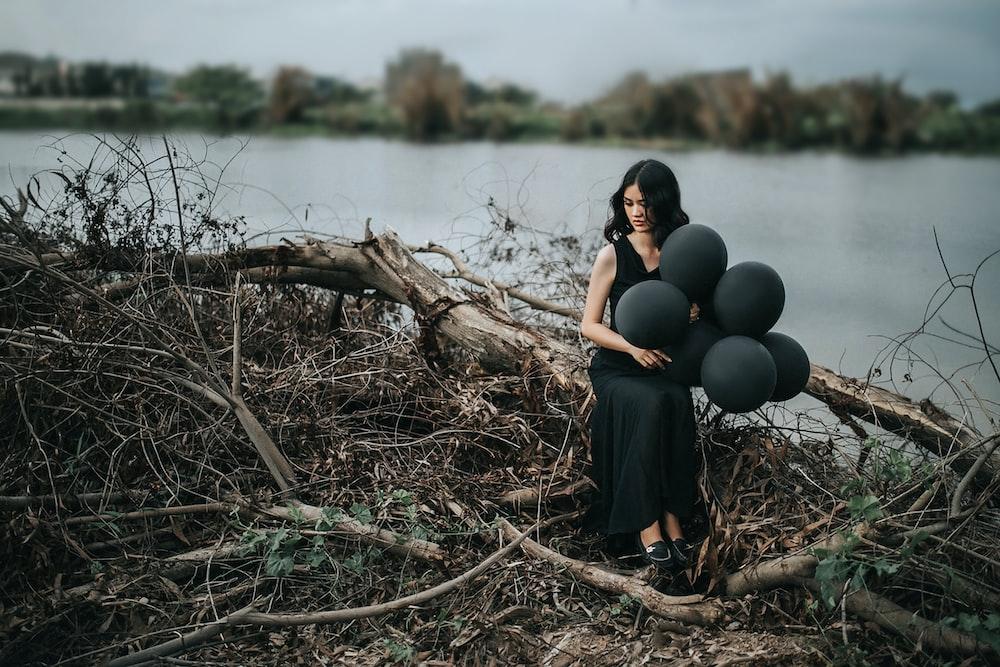 woman in black sleeveless dress holding balloons