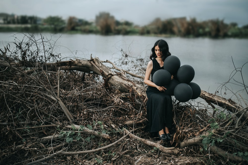 woman in black sleeveless dress holding balloons