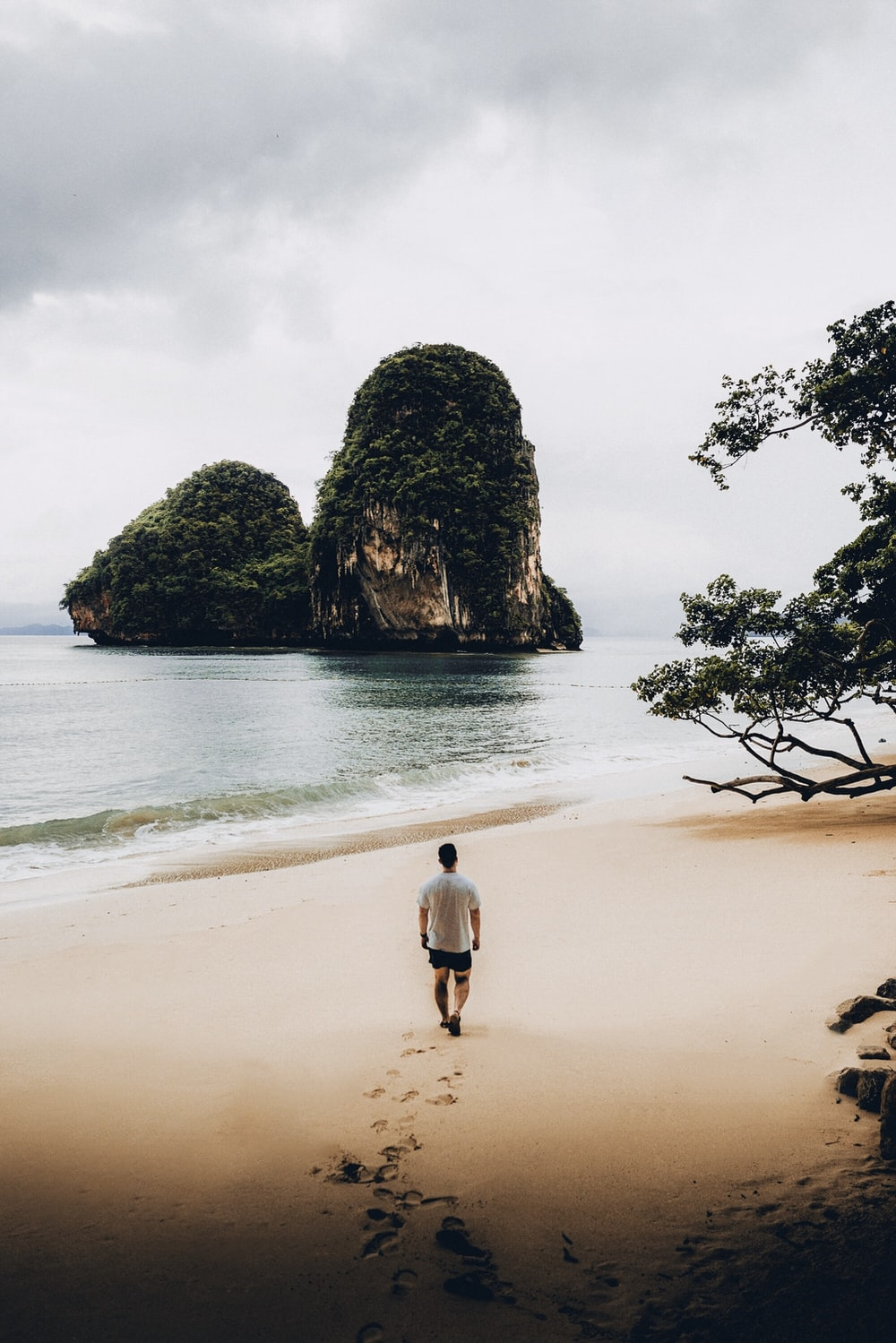 man in white t shirt walking on shore facing two islets