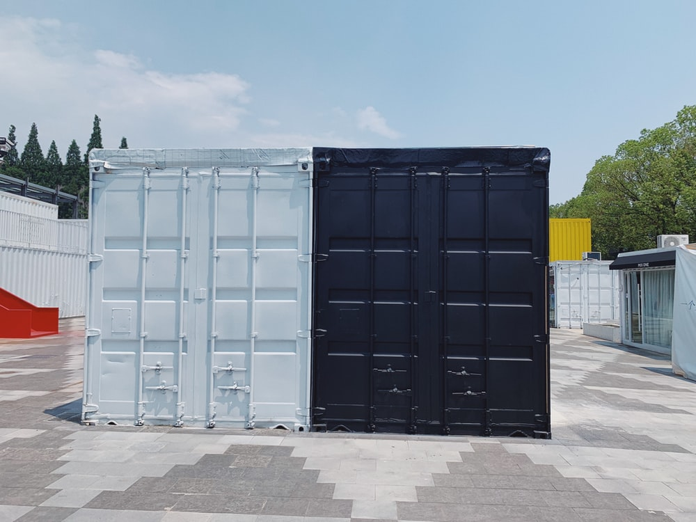 two white and black cargo containers near trees