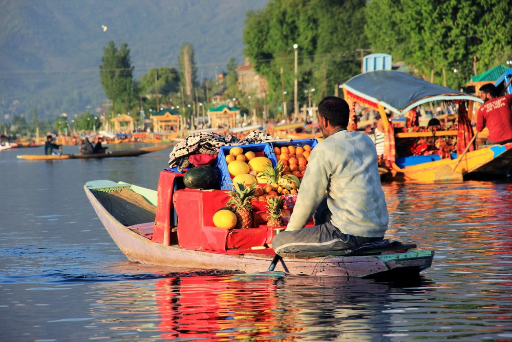 man sitting on boat selling different fruits