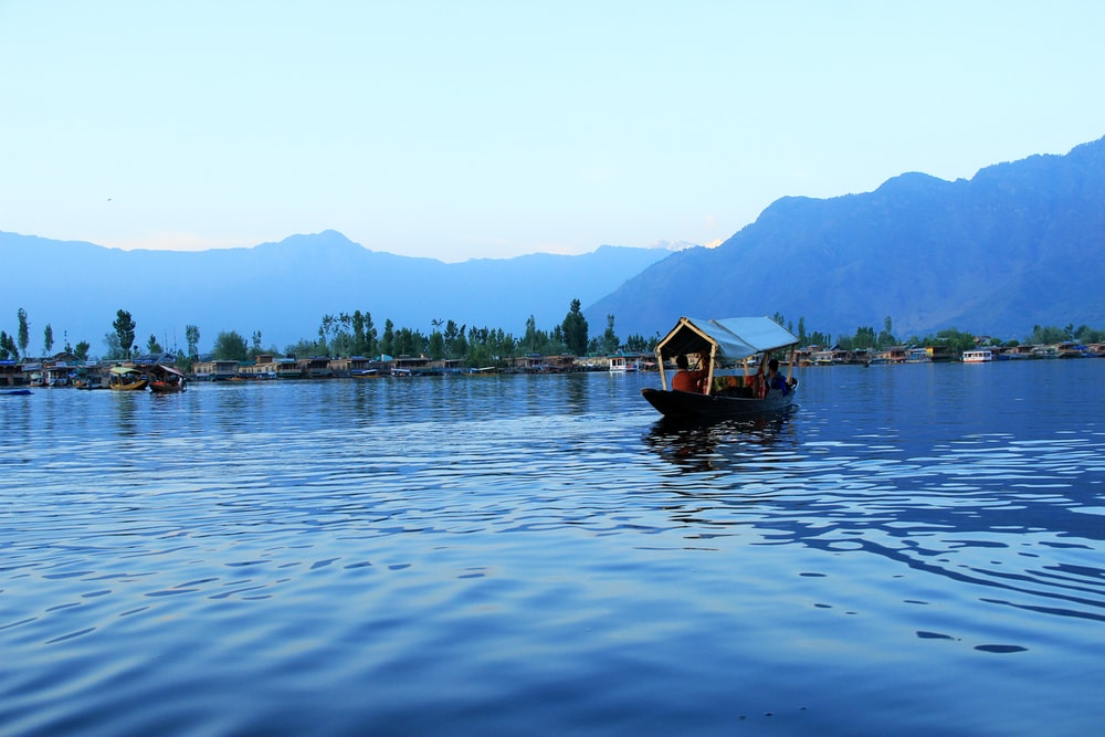 people riding boat on body of water near island