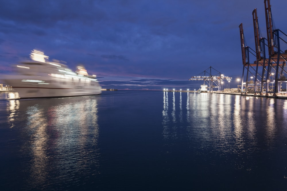 white cruise ship on calm body of water