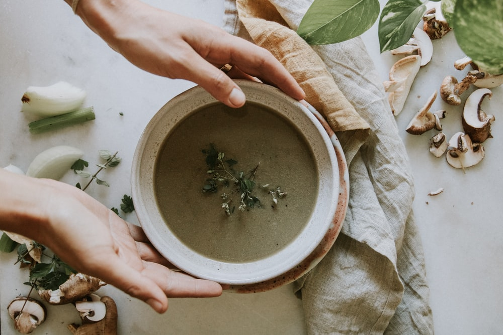 person holding bowl with soup