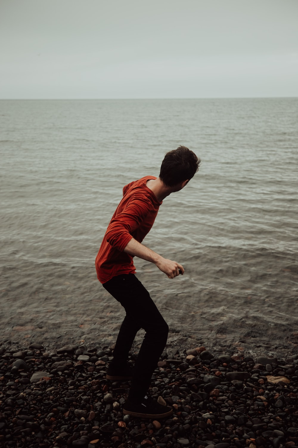 man wearing red shirt about to throw stone on ocean