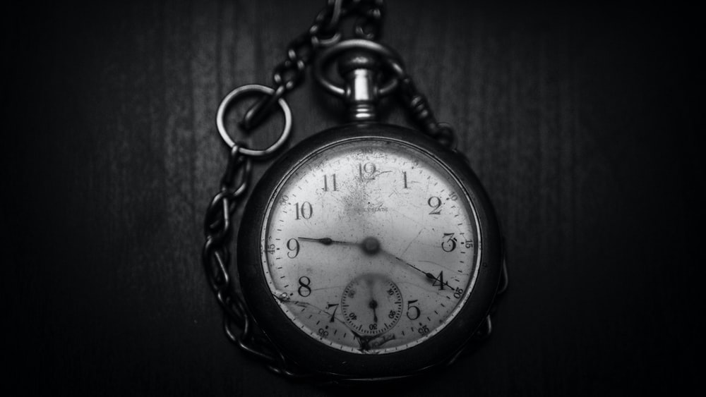round silver-colored analog pocket watch