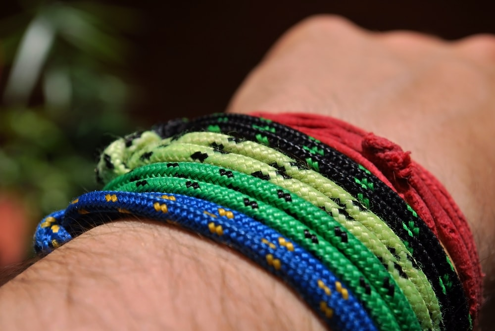 person wearing assorted color cord bracelets