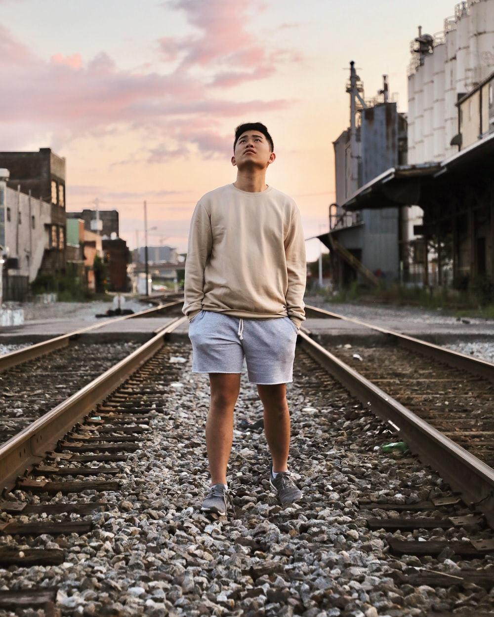 man wearing gray sweater standing on railway looking up