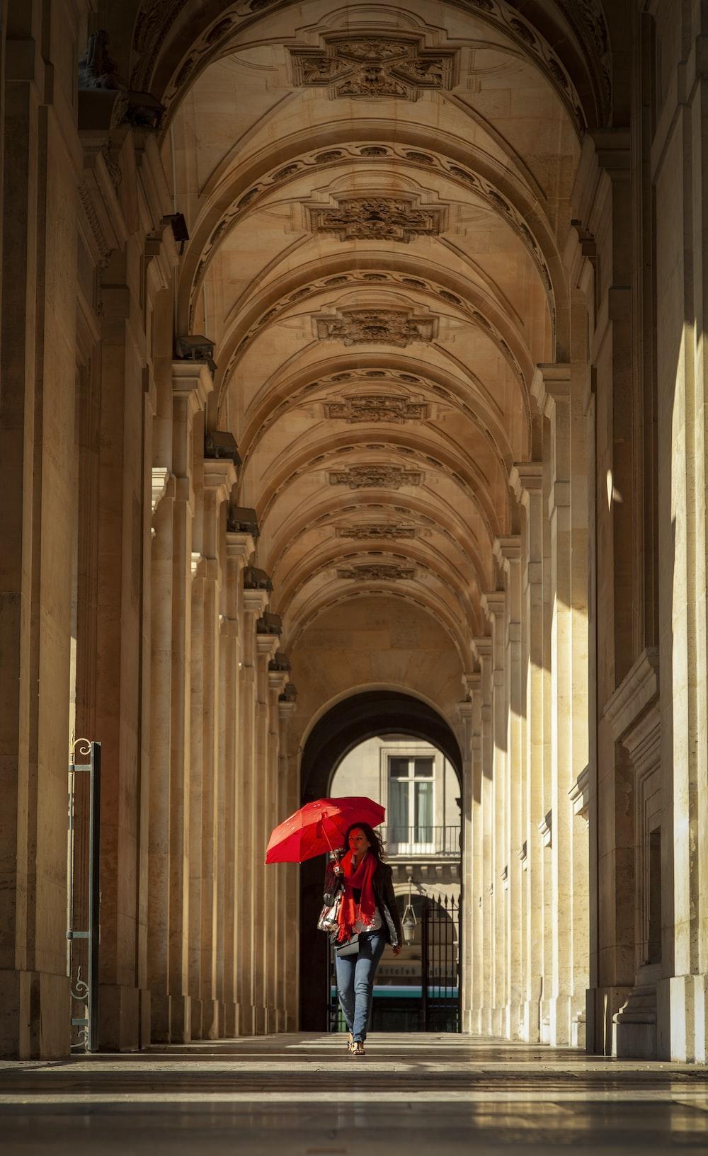 walking holding umbrella walking on building corridor