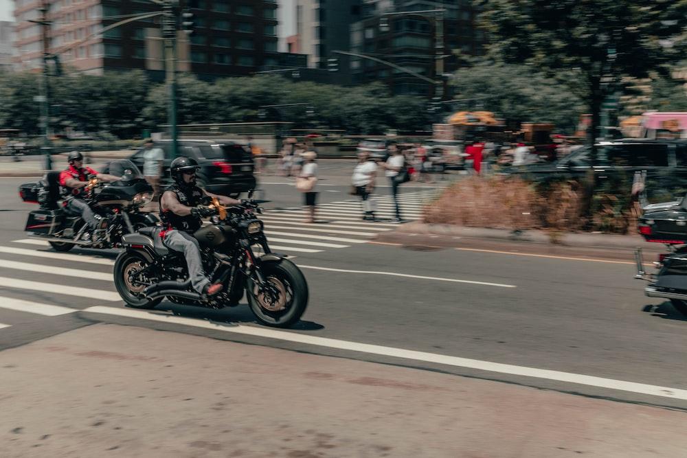 man riding motorcycle viewing people walking near road