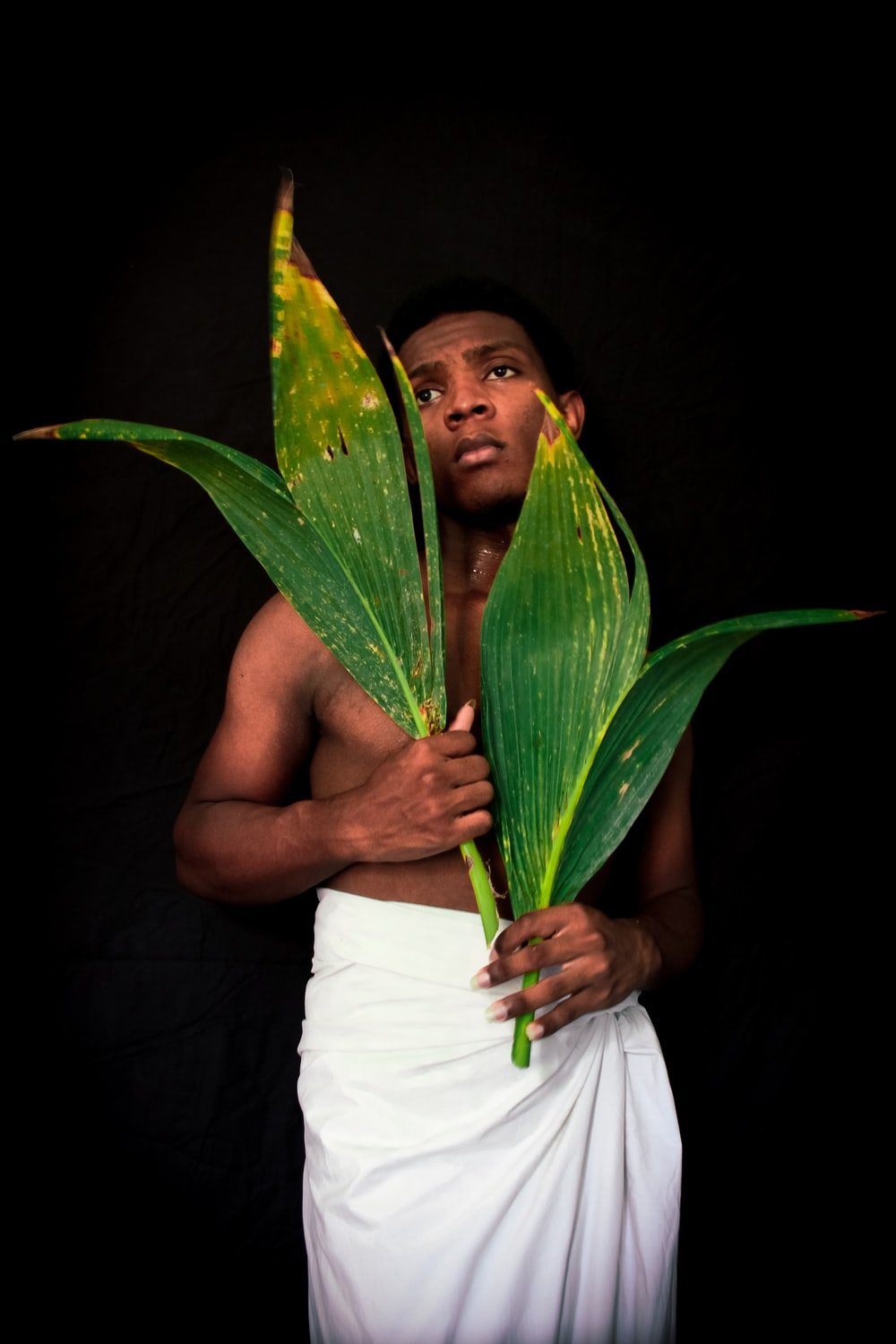 man holding coconut leaves