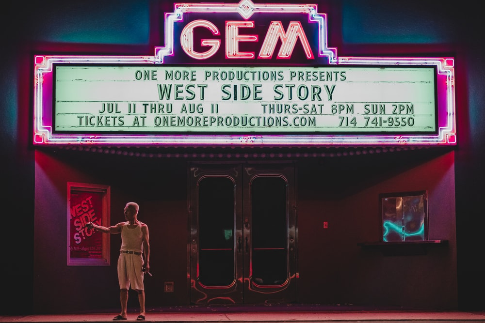 man standing in front GEM movie house