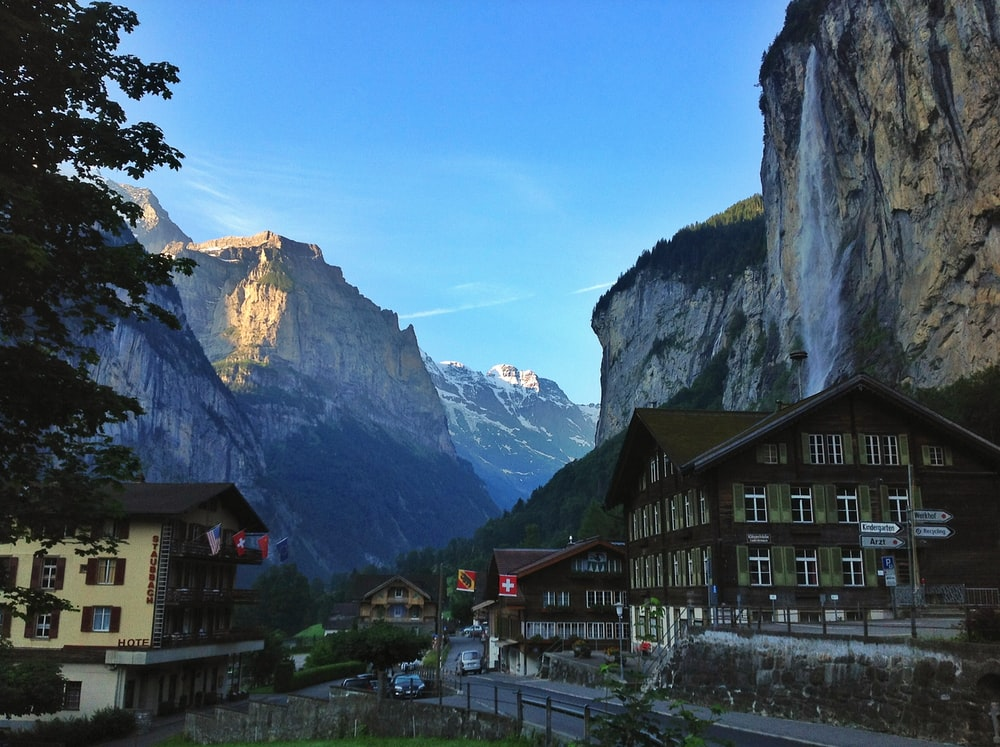 photography of buildings beside mountain cliff during daytime
