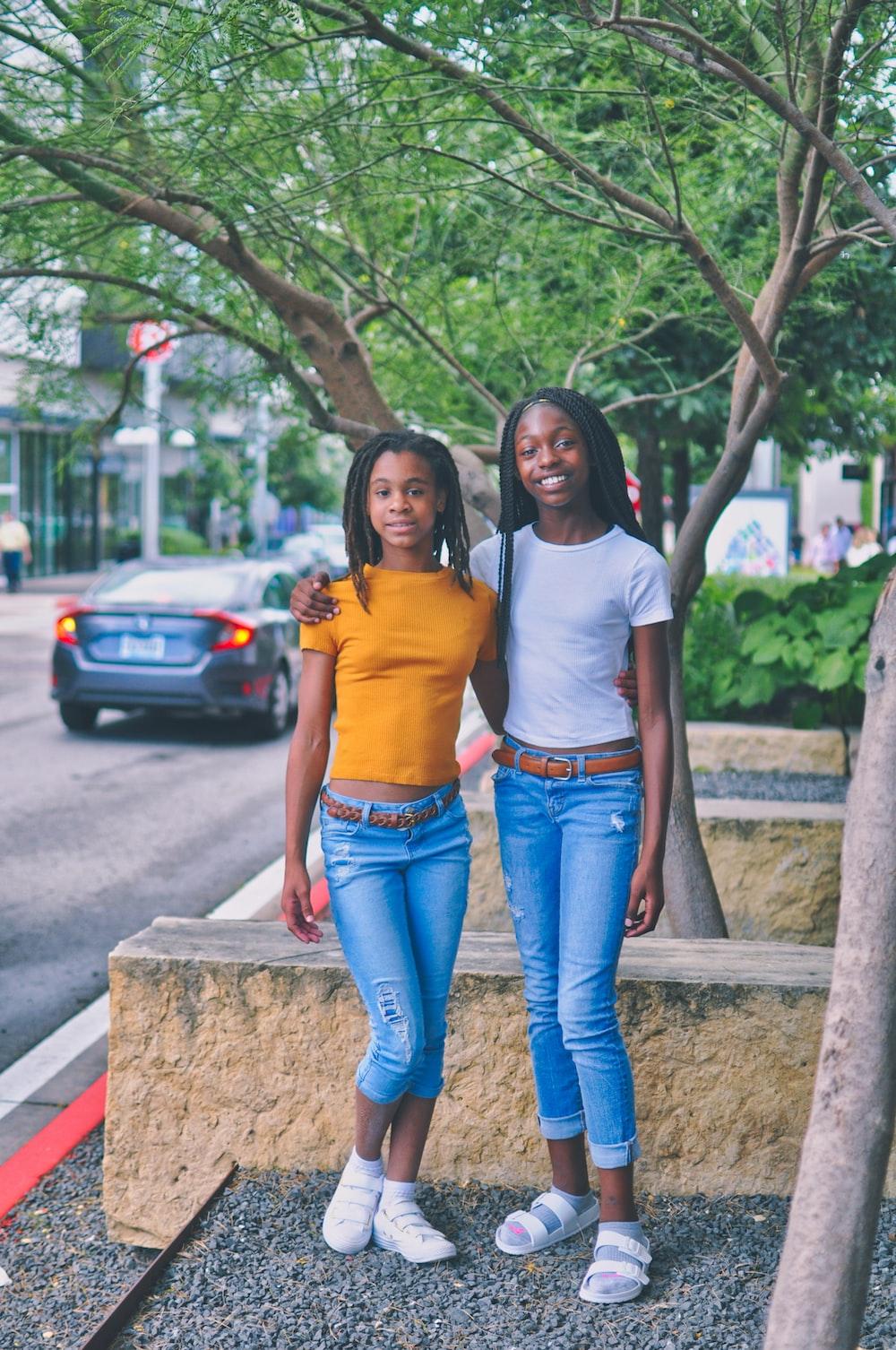 two girls standing near tree