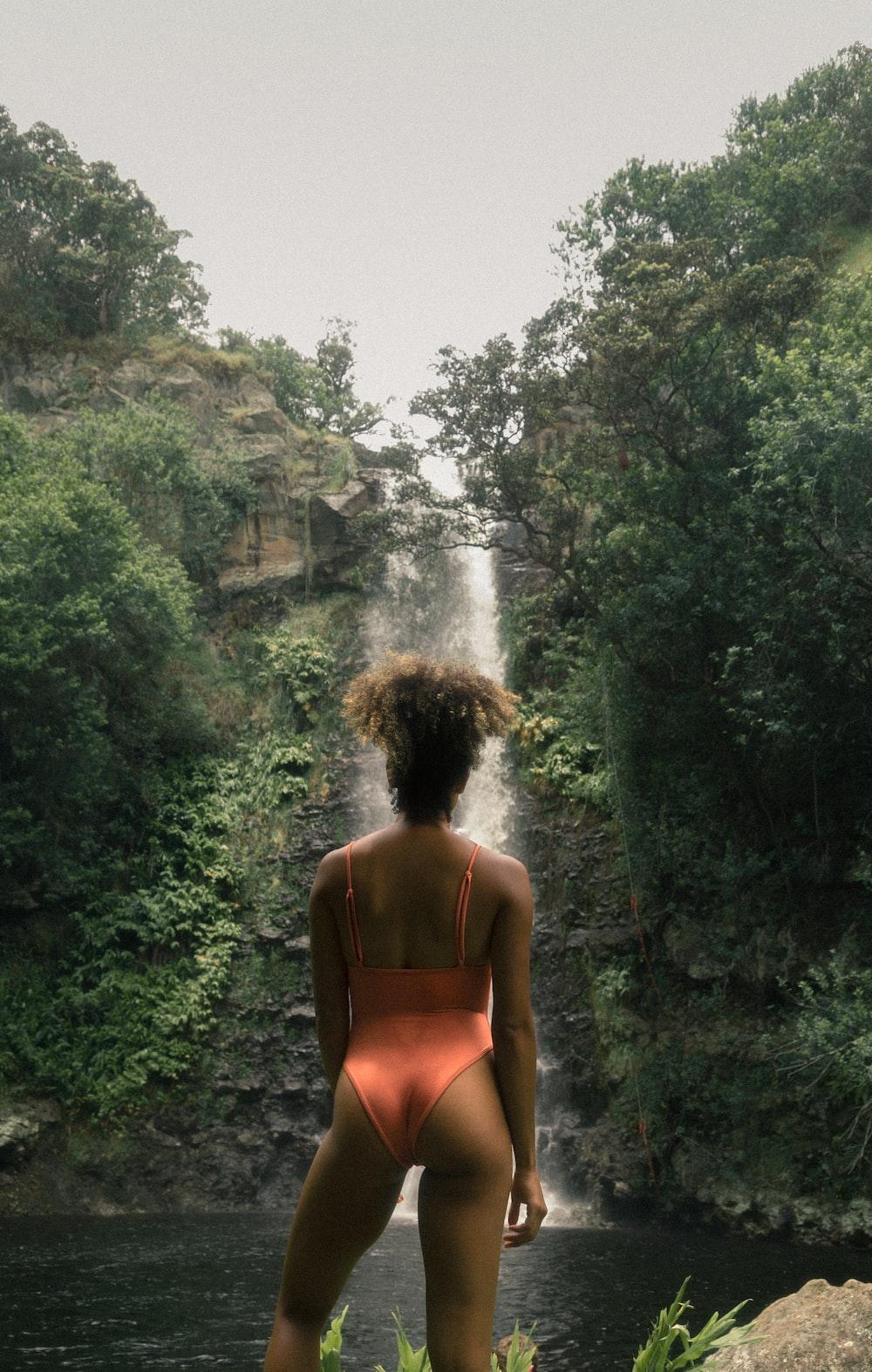 woman wearing orange swimsuit facing waterfalls