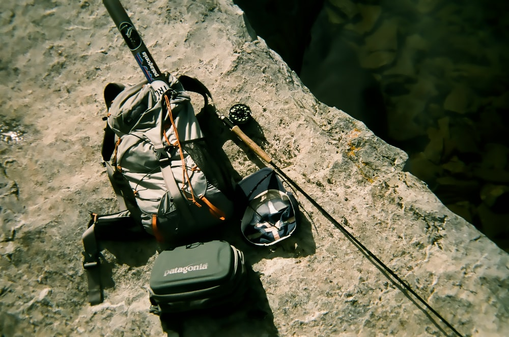 backpack and fishing rod on rock