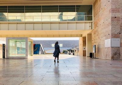 walking person wearing robe under bridge constructivism zoom background