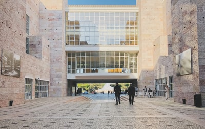 people walking on pathway near buildings constructivism zoom background