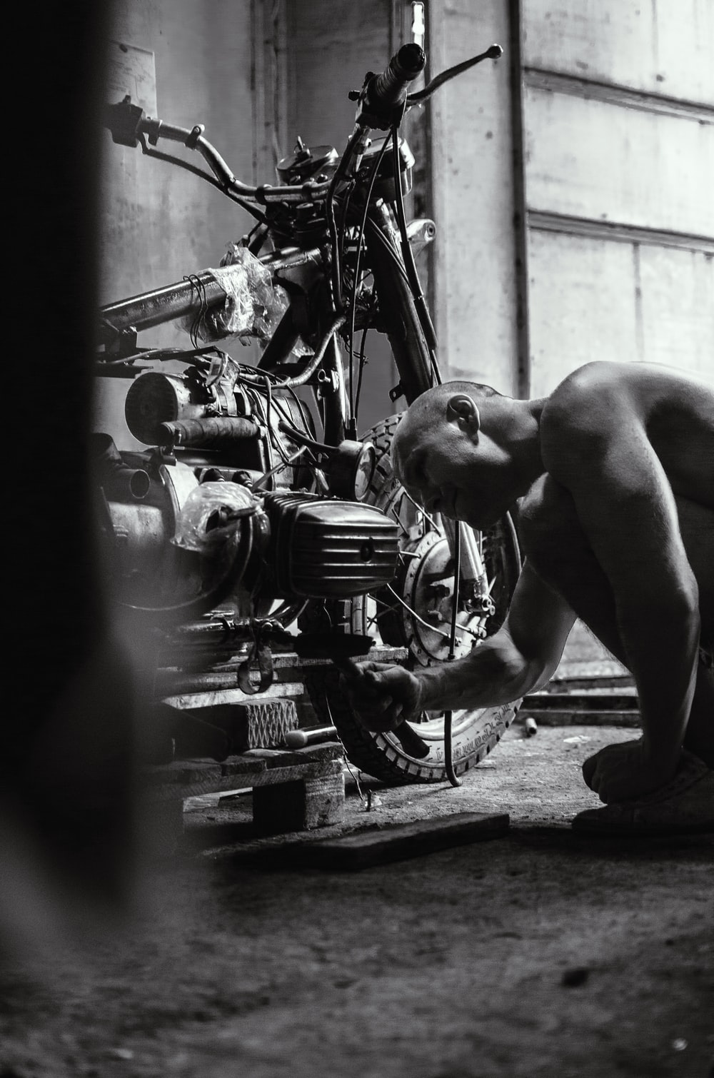 grayscale photography of man fixing motorcycle