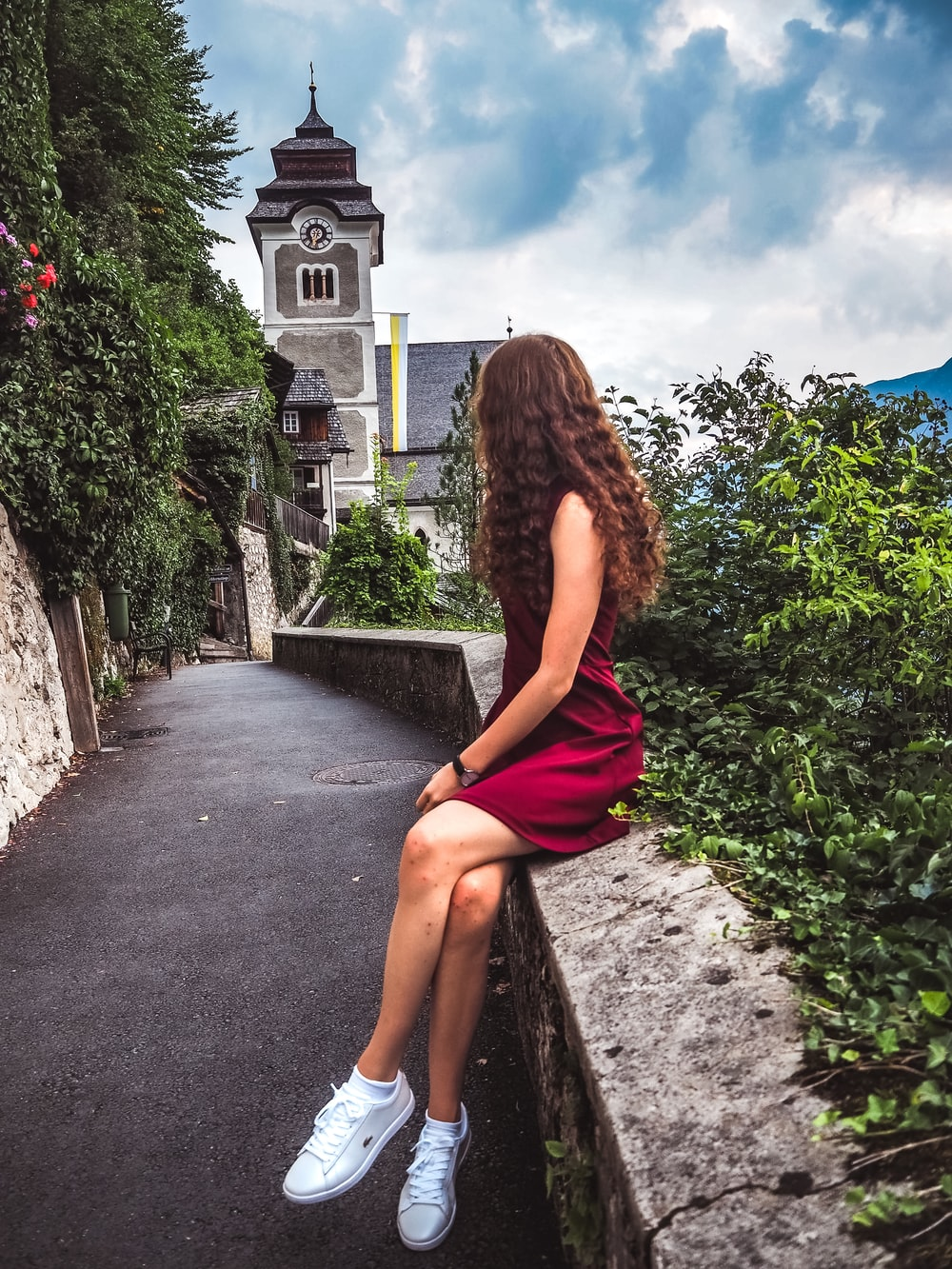 woman sitting on concrete wall near a cathedral