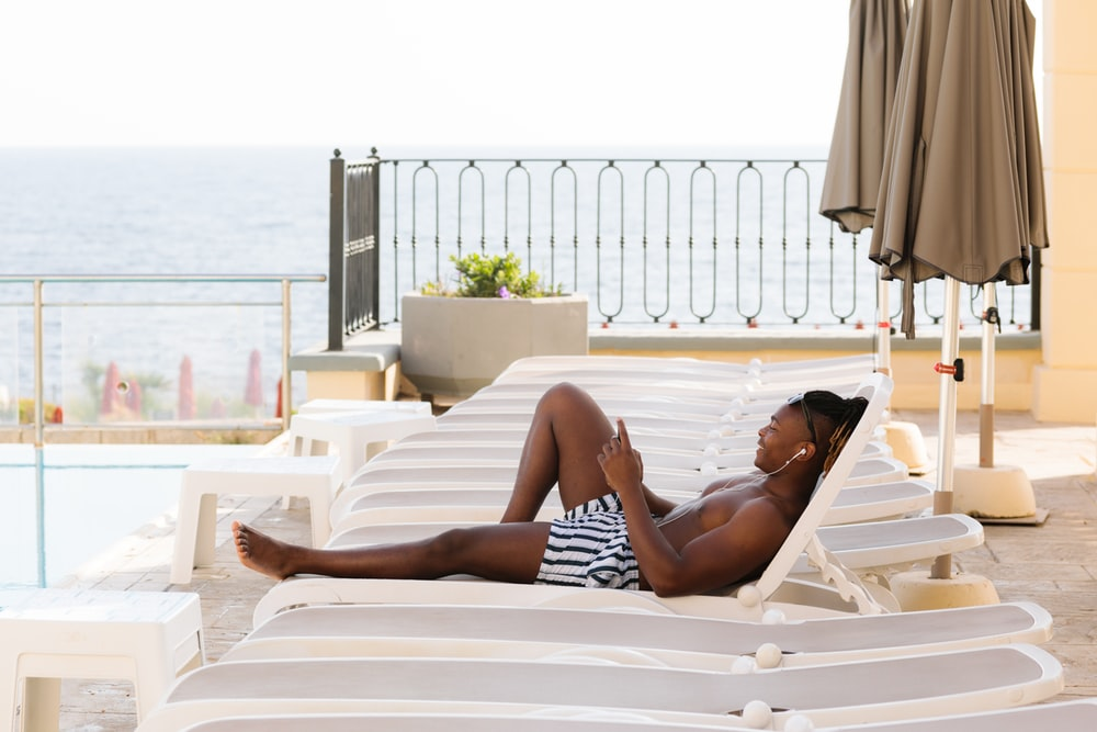 topless man lying on sunlounger with earphones