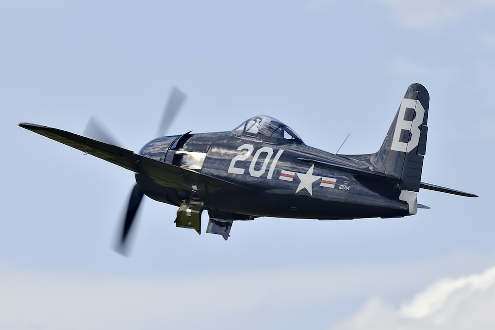 shallow focus photo of black monoplane flying during daytime