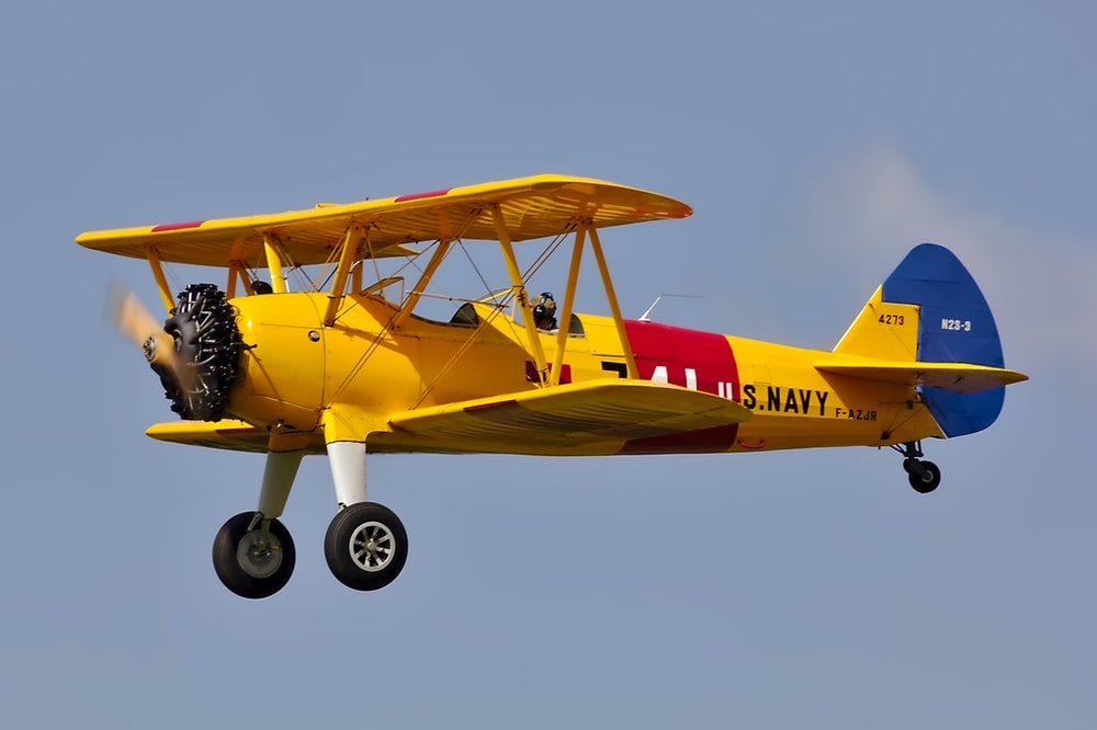 yellow, red, and blue bi-plane flying under blue sky