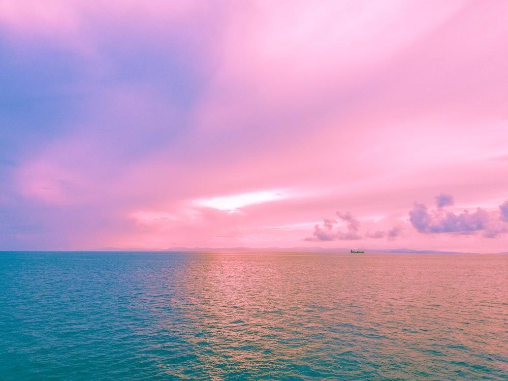 body of water under pink sky