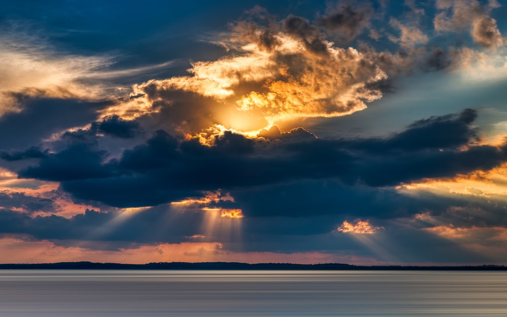 crepuscular photography of rays from cumulus clouds into the sea