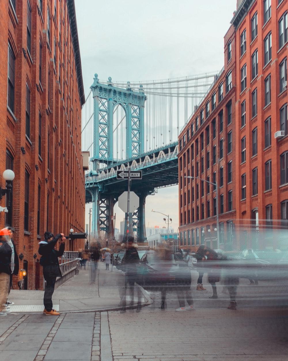 people near orange building and bridge during daytime