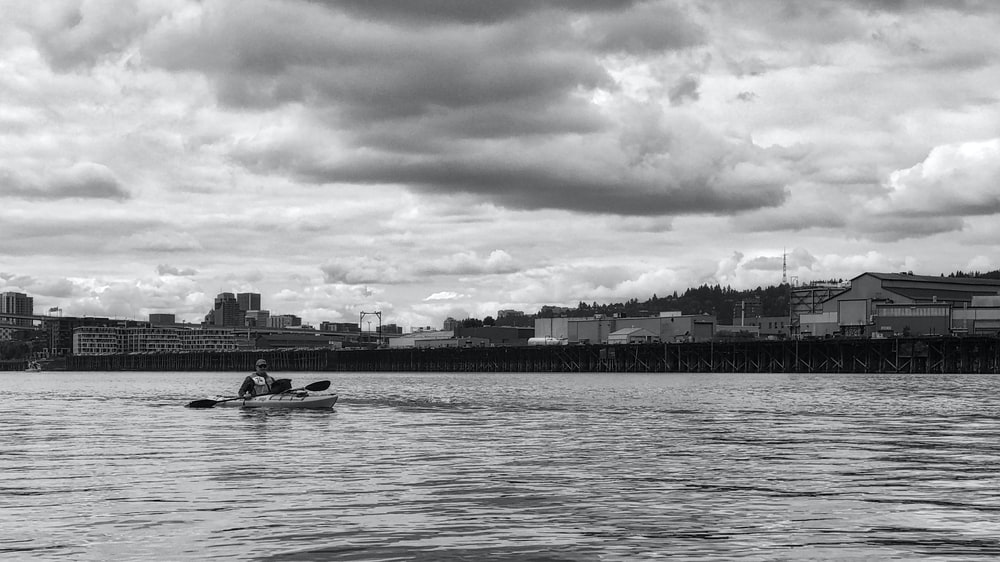 grayscale photography of man riding boat on body of water and cityscape