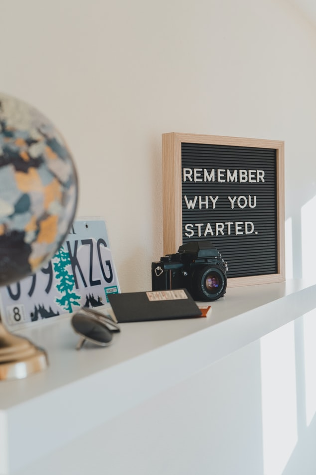 "A photo of a ledge shelf with a few knicknacks on it, an old SLR camera, and a sign board that says ""remember why you started"" on it"