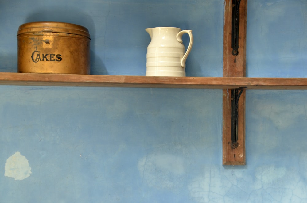 white ceramic teapot near brown cakes tin can on brown wooden floating shelf