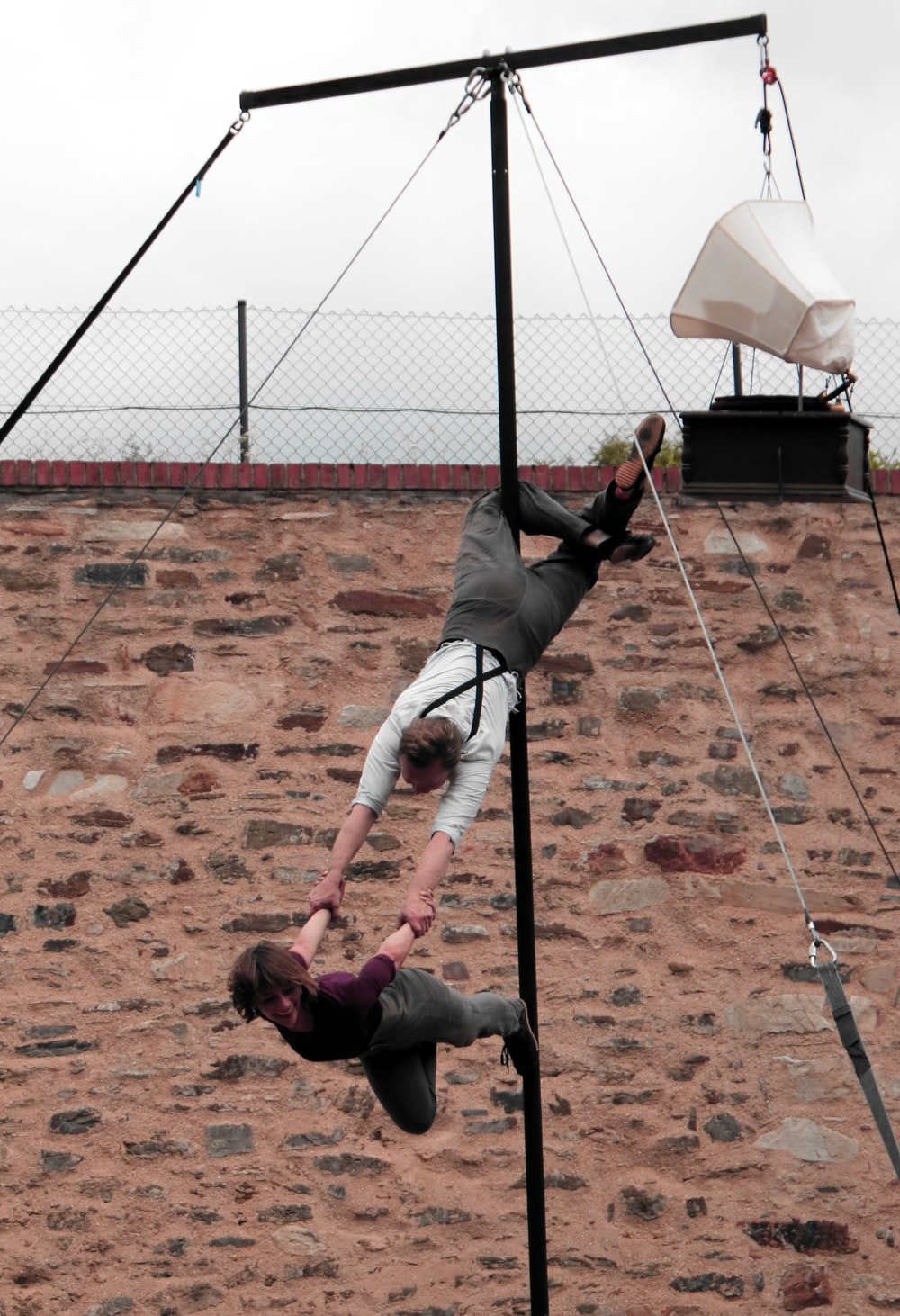 man hanging on rod carrying woman