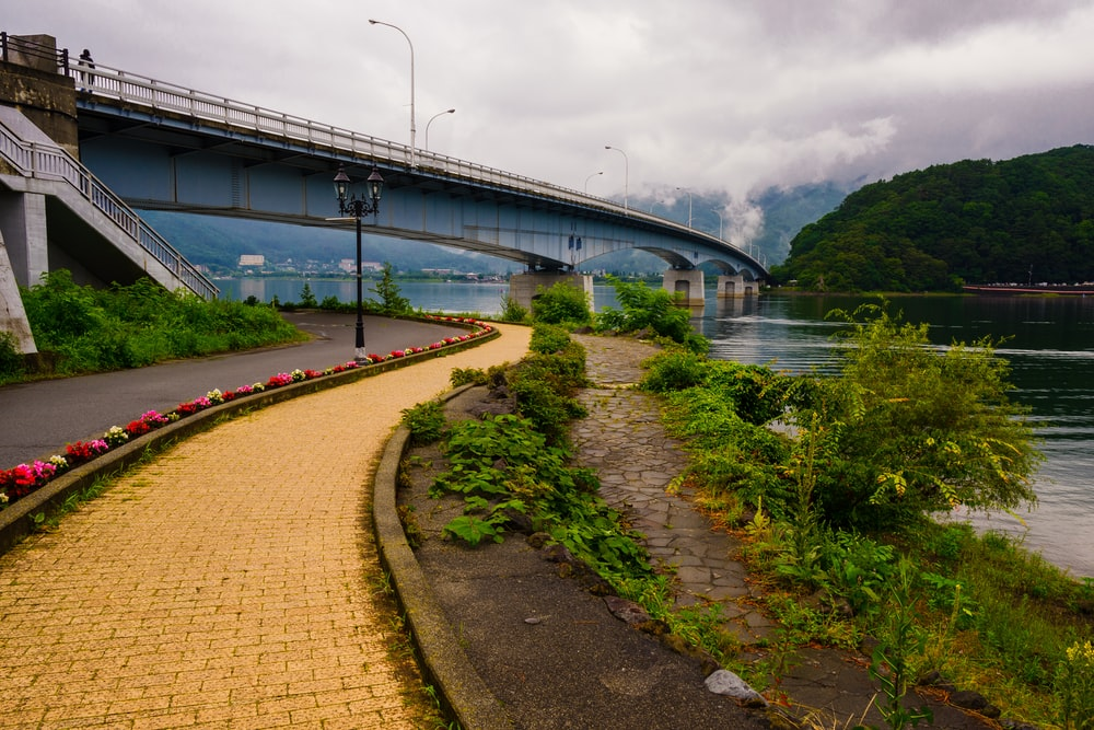 gray concrete road viewing lake and bridge under white cloudy skies