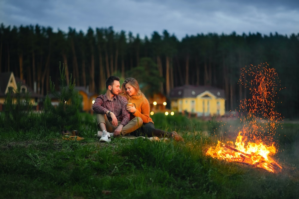 shallow focus photo of man and woman sitting on grass beside fire pit