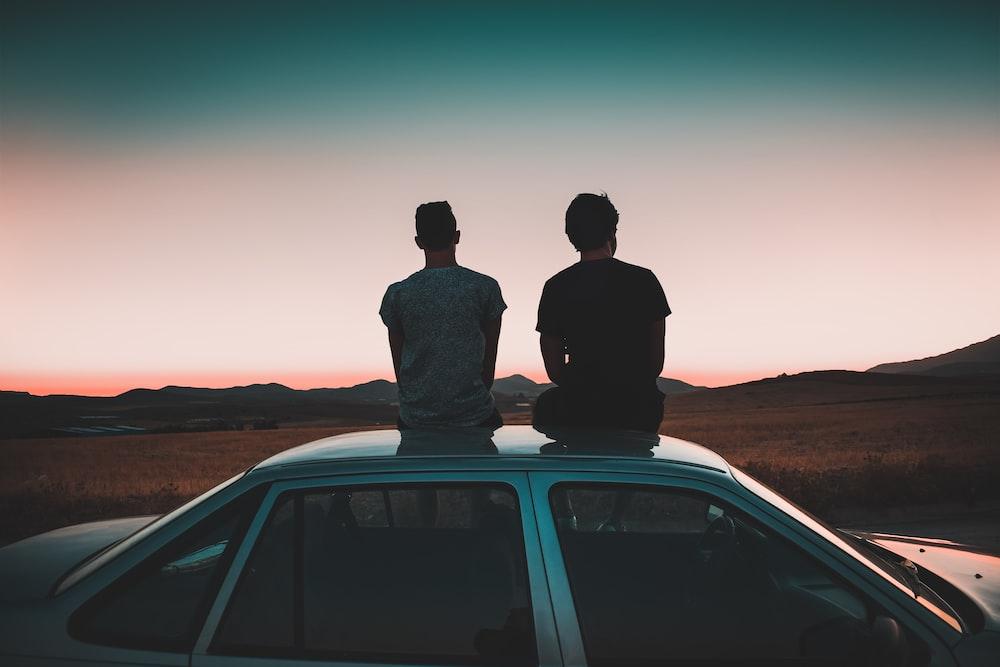 two men sitting on vehicle