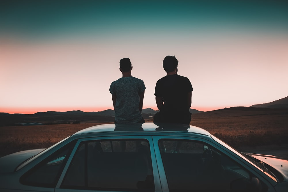 two men sitting on vehicle