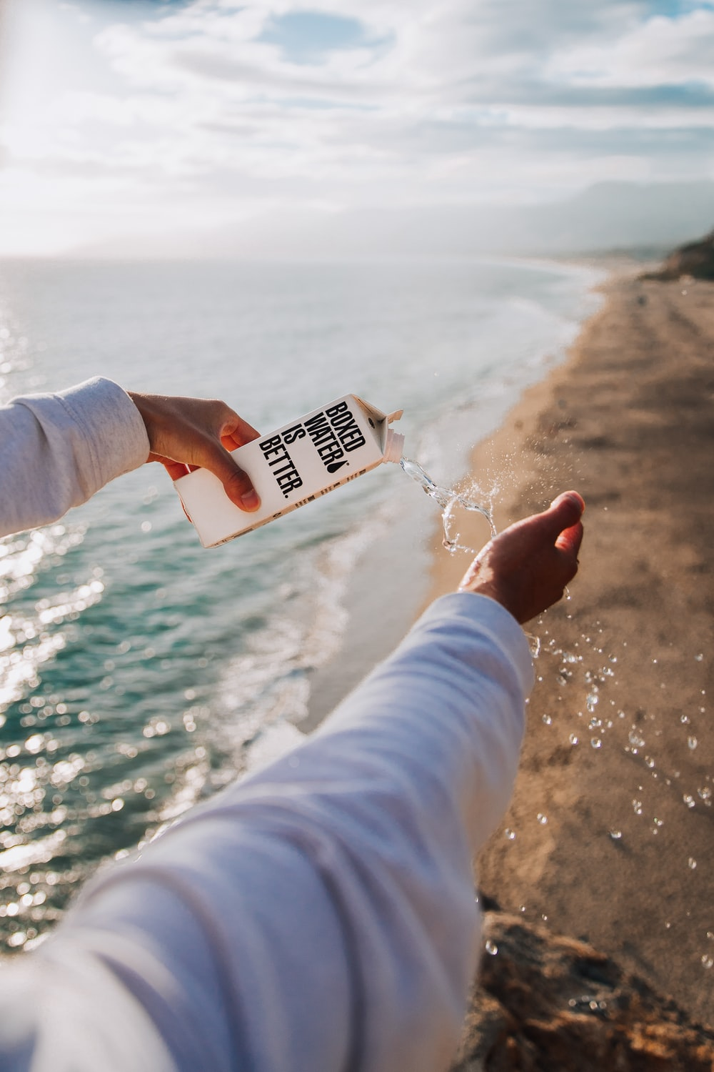 person holding boxed water across seashore
