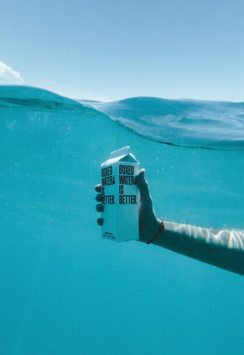 person holding boxed water underwater