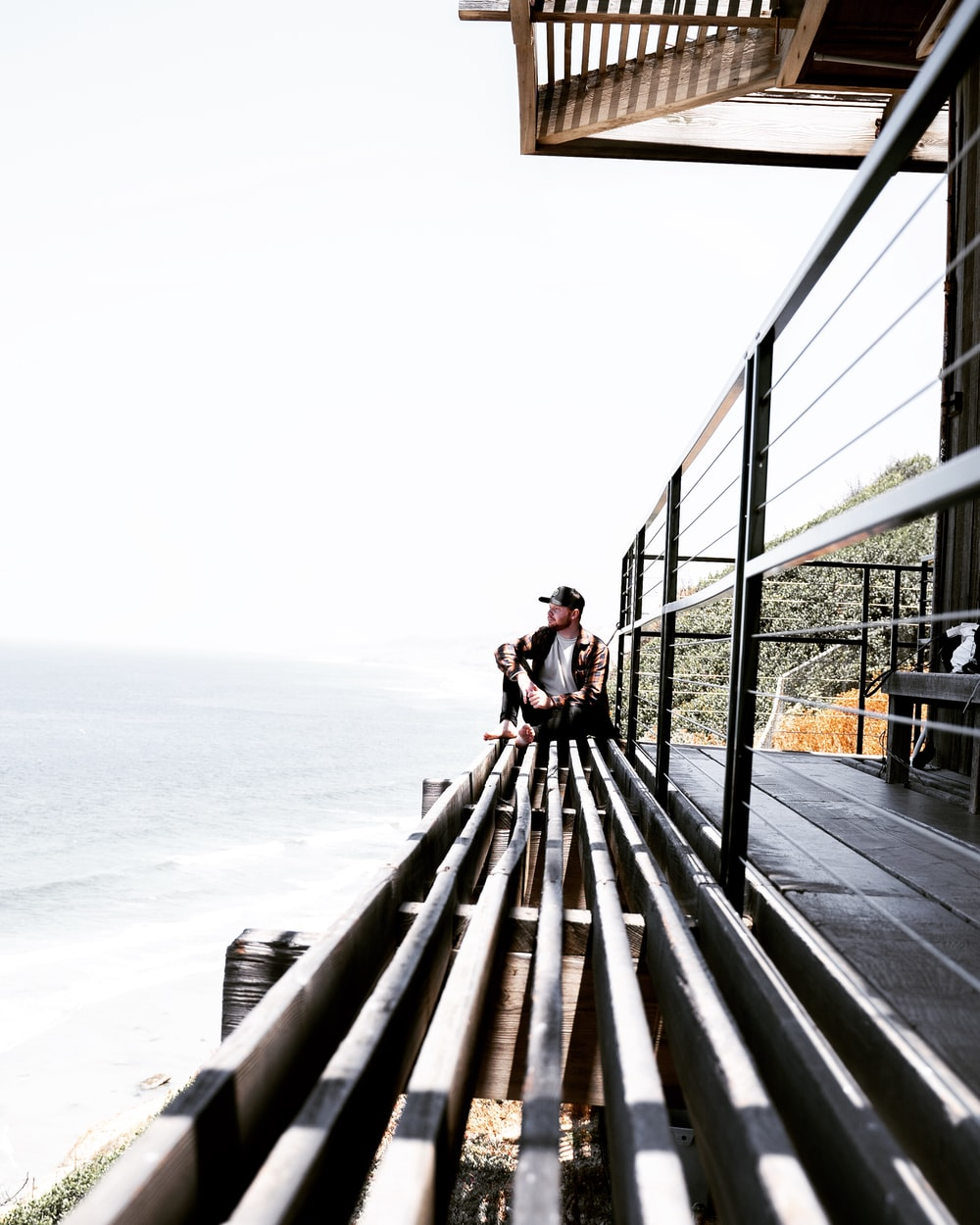 man sitting on grey surface near ocean