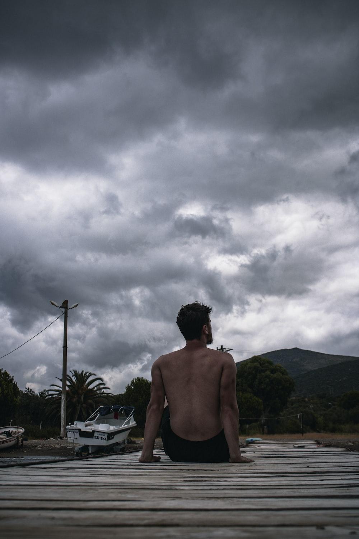topless man sitting on dock