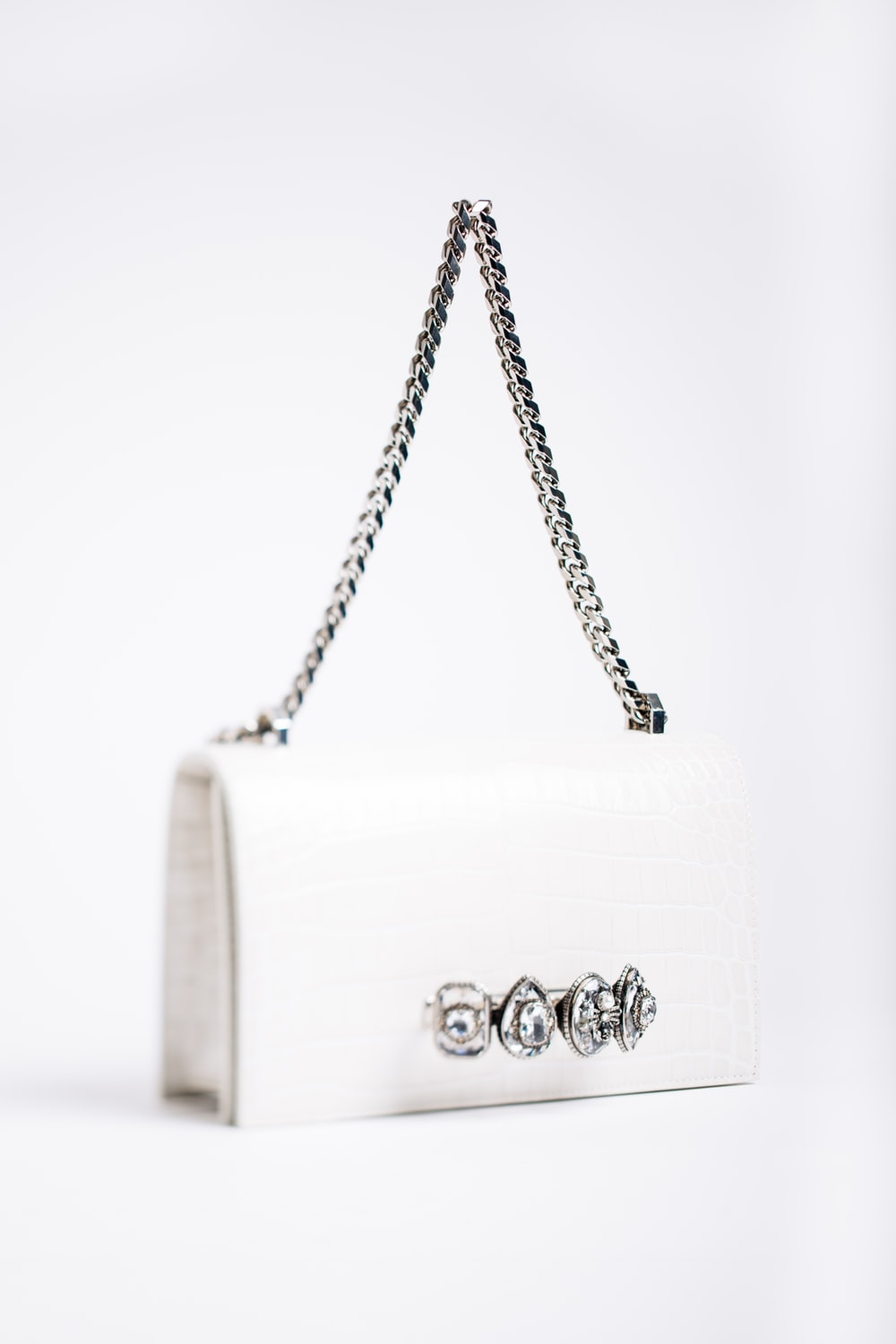 white handbag with silver chain handle