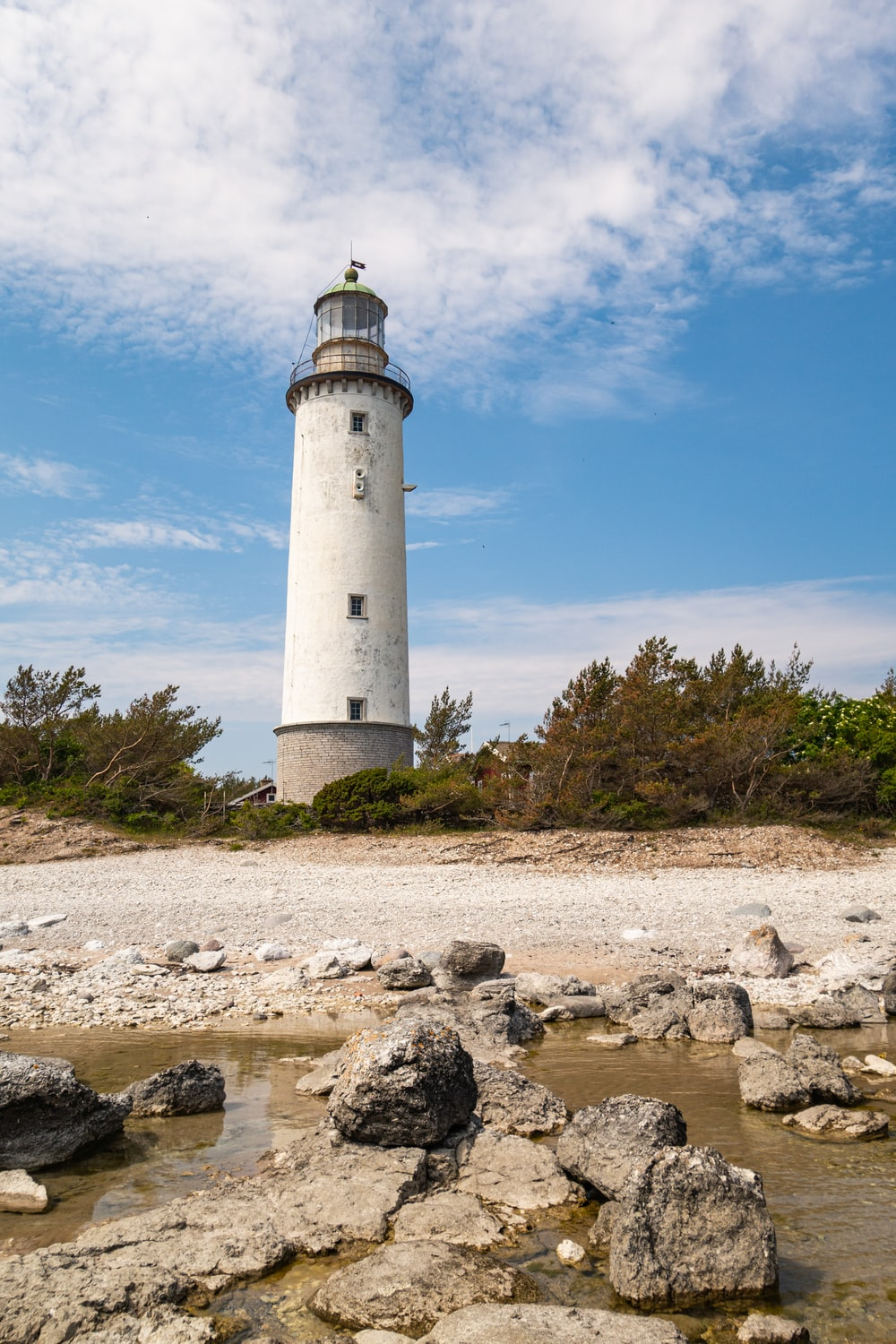 white lighthouse at the shore during daytime